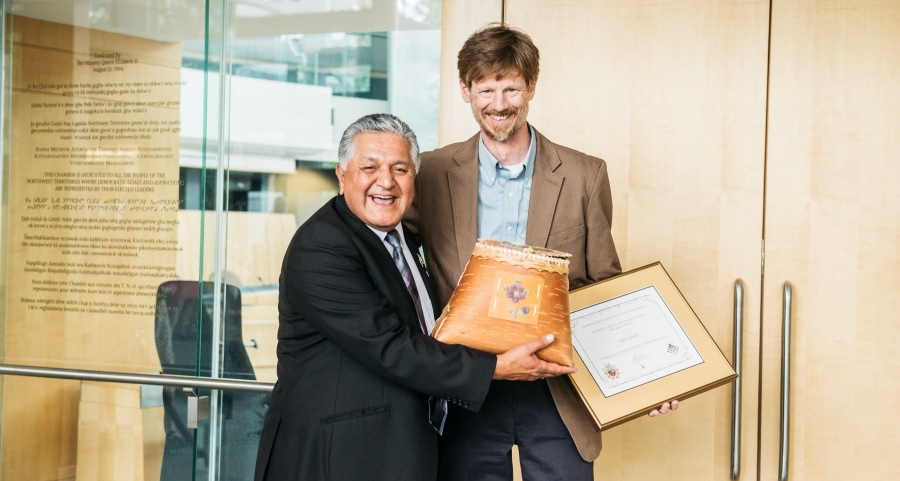 George L. Tuccaro, Commissioner of the NWT, presents Scott Duke, Legal Counsel, with a birch basket and certificate of his award.